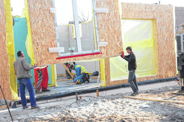 Contractors install modular frame plywood board panel walls house on the home construction site in 2018 in Kyiv, Ukraine. Oriented Strand Board now fetches a higher price as increased demand and tight supplies lead to delivery delays and elevated construction costs in the U.S. and Canada.