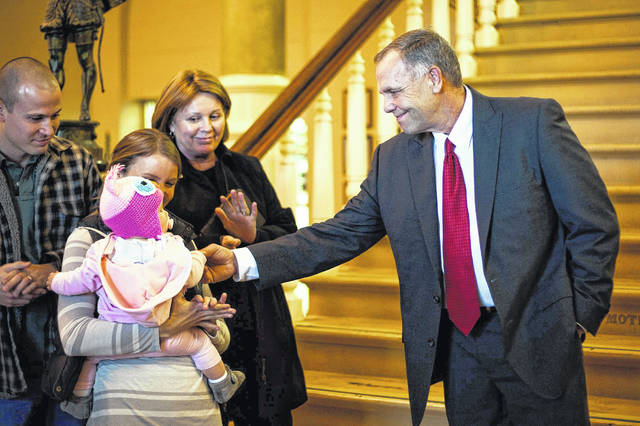 Allen County Commissioner-elect, Jay Begg, celebrates with granddaughter Emersyn Lee, held by daughter Brittany Lee, after taking the oath of office at the Allen County Courthouse on Friday, December 28, 2012 in Lima (L.M. Parr - The Lima News)