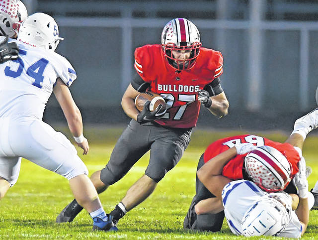 Columbus Grove's Colin Metzger looks for a running lane during Friday night's Northwest Conference championship game against Allen East at Columbus Grove. See more game photos at LimaScores.com.