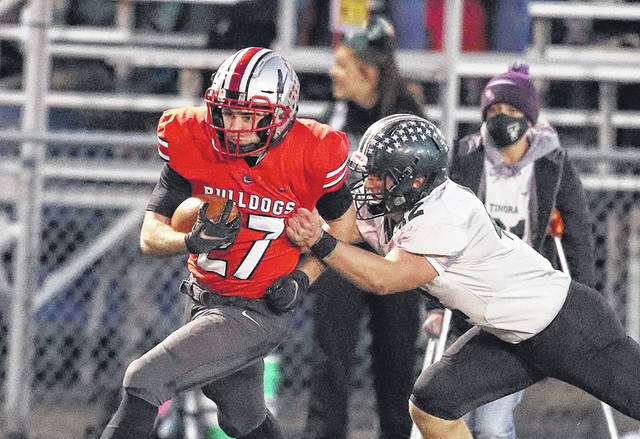 Columbus Grove's Colin Metzger looks for more yardage after making a catch during Saturday night's Division VI playoff game against Tinora at Columbus Grove. See more game photos at LimaScores.com.