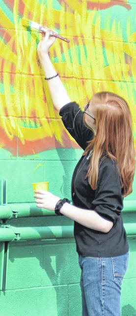 Paige Talboom, a freshman at Shawnee High School, adds some color to the new mural at Our Daily Bread Community Center.