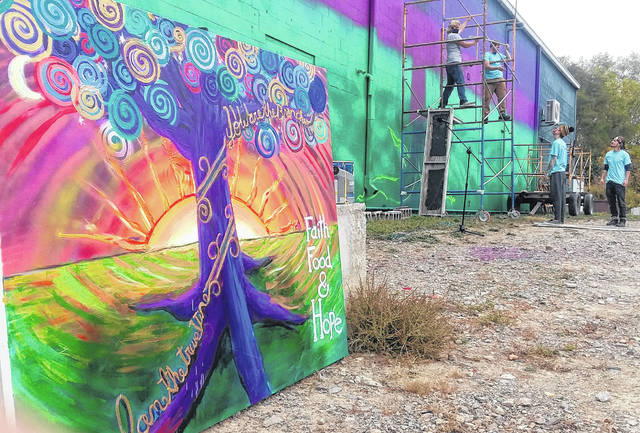 Work began Sunday on a new mural outside of Our Daily Bread Community Center in Lima.