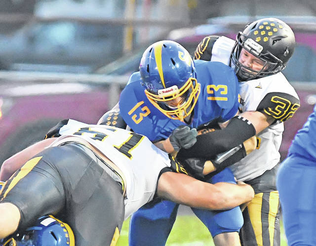 Clay Paddubny of Delphos St. John's fights for yardage against Hardin Northern's Mason Roby, left, and Brock Hipsher during Friday night's Division VII playoff game at Stadium Park in Delphos.