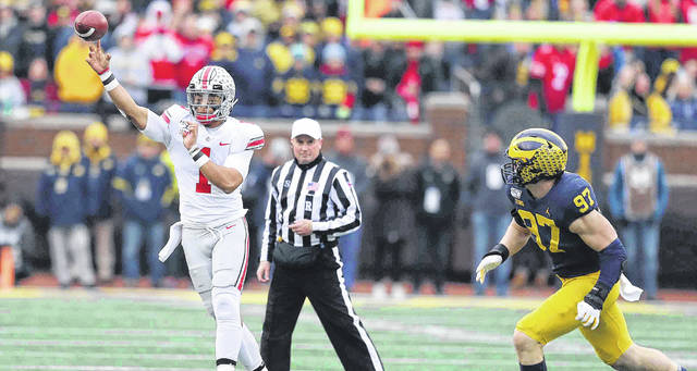 Justin Fields throws a pass while Michigan defensive lineman Aidan Hutchinson (97) arrives too late to apply pressure during last year's game in Ann Arbor.