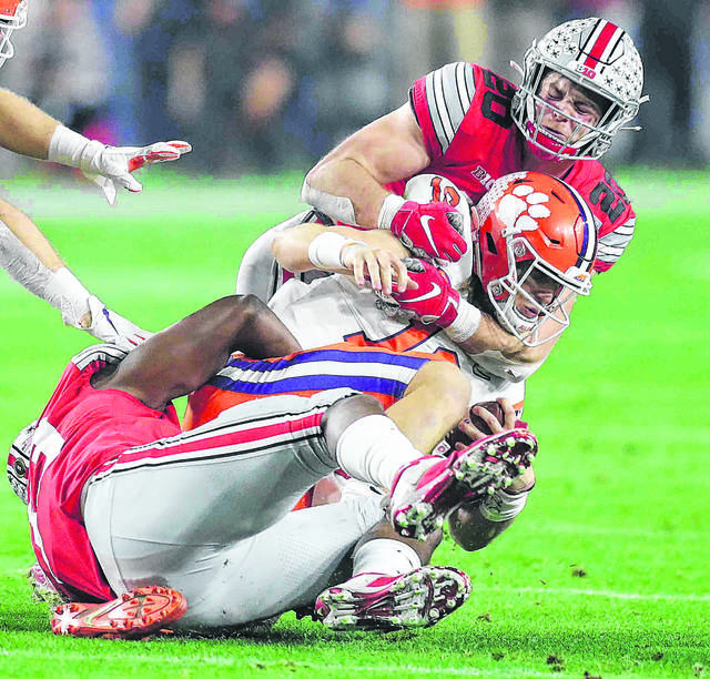 Ohio State defensive end Zach Harrison (bottom) and linebacker Pete Werner (20) wrap up Clemson quarterback Trevor Lawrence during a College Football Playoff semifinal last season.
