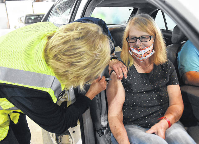 Diana Schulz, left, a registered nurse with the Auglaize County Health Department gives Anna Fisher, of Wapakoneta, her yearly flu shot during a Drive-Thru Flu Vaccine Clinic held at the Auglaize County Fairgrounds on Wednesday. Students from Wright State were also on hand to give flu shots. Rhodes Medical Assisting students also assist with registration, screenings during the five two-hour shifts.