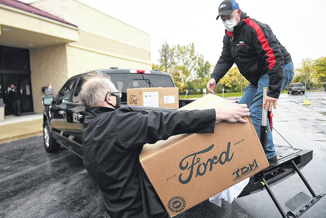 Judd Templin, left, and Bob Stewart, employees with Ford Motor Company, load boxes of 100,000 pieces of PPE. The plant donated the supplies to the City of Lima.