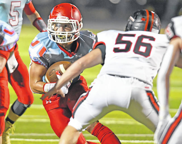 Lima Central Catholic's Rossy Moore looks to get past Mohawk's Tyler Spoon during Friday's Division VII playoff game at Spartan Stadium.
