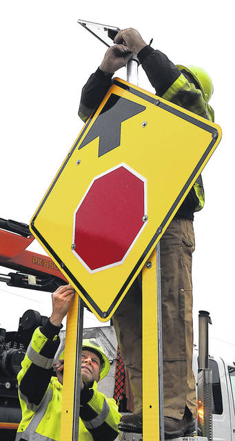 "Larry Kaughfam, left, and Glen Wurth install four new signs using LED flashing lights two ""stop ahead"" signs on Fort Amanda Road and two ""crossroads ahead"" on state Route 501. The Ohio Department of Transportation removed the overhead flashing light at the intersection, replacing it with the four signs and LED flashing lights to notify drivers of the intersection head. Work was performed by the Ohio Department of Transportation District 1's roadway services."