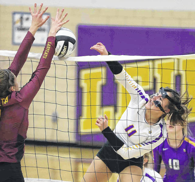 Leipsic's Marisa Hermiller (11) hits a spike against Kalida's Brooke Erhart during Thursday night's match at Leipsic.