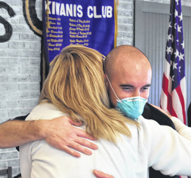 Lima resident Hellen Douglas threw her arms around firefighter Matt Hammons Tuesday when the LFD fireman made a surprise visit to the Lima Kiwanis Club meeting. Douglas was on hand to accept a club donation to the Family Promise organization.