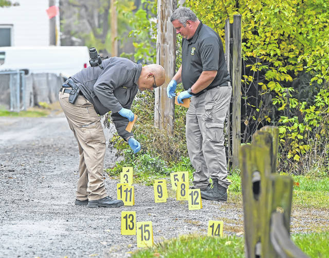 Detectives investigate shell casings found in an alley in the 400 block of North Charles Street on Tuesday afternoon.