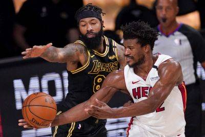 Thje Los Angeles Lakers' Markieff Morris, left, and the Miami Heat's Jimmy Butler battle for a rebound during Game 5 of the NBA Finals on Friday night in Lake Buena Vista, Fla. (AP photo)