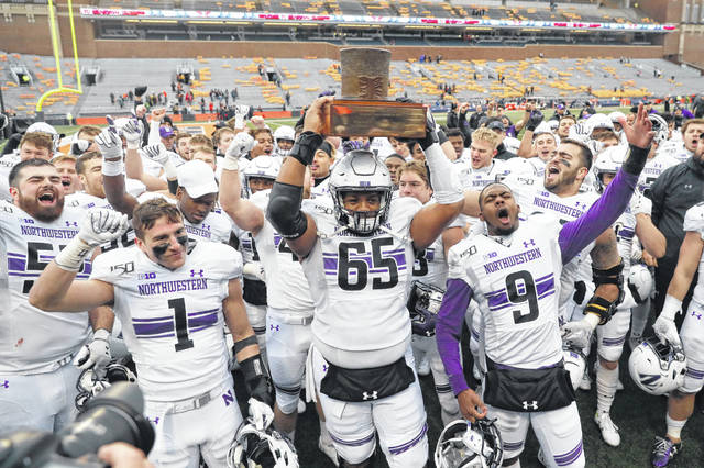 Northwestern's football team celebrates with the Land of Lincoln trophy after beating in-state rival Illinois last season.