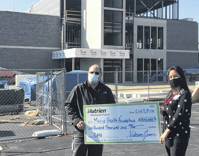 Nutiren Lima General Manager Todd Sutton (left) presents a check to Mercy Health Lima market President Ronda Lehman on Wednesday outside the future Graduate Medical Education Center.