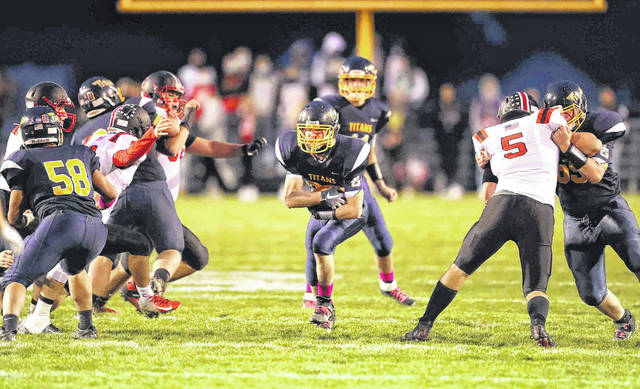 Ottawa-Glandorf's Marco Rosales (58) and Cael Hoehn, right, clear a path for Parker Schnipke during Saturday night's Division V playoff game against Orrville at Ottawa-Glandorf. See more game photos at LimaScores.com.