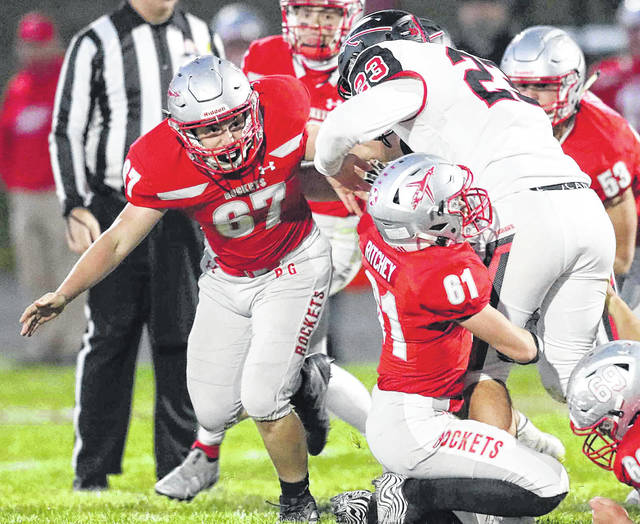 Pandora-Gilboa's Charles Ritchey (61) gets a hold of Sycamore Mohawk's Mason Danner as Wyatt Russell (67) closes in to help with the tackle during Friday night's Division VII playoff game at Pandora-Gilboa.