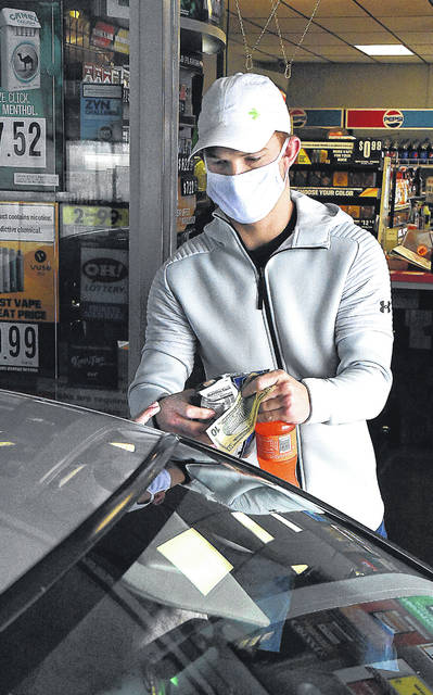 Ryan Tabler of Tabler Drive-Thru in Columbus Grove wears a mask while waiting on a customer Thursday.