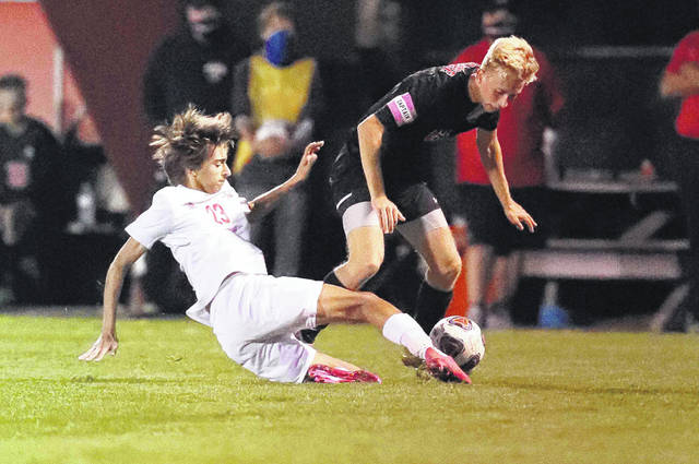 Wapakoneta's Connor Lause slides to get to the ball ahead of Shawnee's Carter Jensen during Thursday night's Division II sectional finakl at Shawnee. See more match photos on 3C and LimaScores.com.