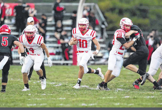 Wapakoneta's Kaden Siefring (4) and Garrett Siefring (20) clear the way for Braeden Goulet during Friday night's Division III playoff game at Shawnee. See more game photos at LimaScores.com.