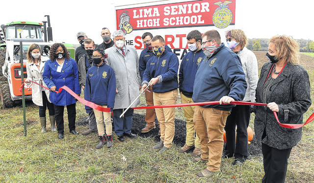 Noah Edwards, president and student advisor for Lima Senior's FFA chapter, cuts the ribbon to officially open Spartan Farm on Tuesday afternoon.