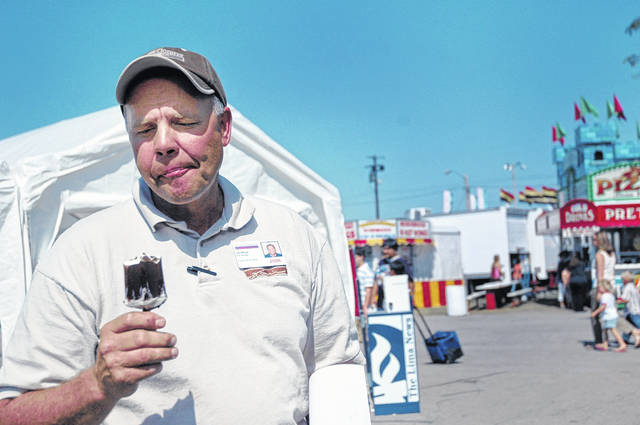 Jay Begg, the Allen County Fair manager, enjoys an ice cream bar while on his way to tend to administrative business. Beggs said that out of all the fair food, he enjoys the ice cream and chocolate milk the best.