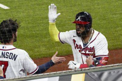 The Atlanta Braves' Marcell Ozuna celebrates after hitting a home run during Thursday's National League Championship game against the Los Angeles Dodgers in Arlington, Texas. (AP photo)