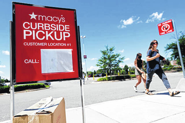 People walk past a curbside pickup sign in June at the Macy's department store in Vernon Hills, Ill. In the days before COVID-19, shopping smart used to mean scoring deals at a department store's weekend sale. But the pandemic has led to a shift in consumer habits. Now, many consumers are making their purchases online for home delivery or picking them up curbside. To save money while shopping during the pandemic, sign up for in-stock alerts, lean on your community, read reviews carefully and more.