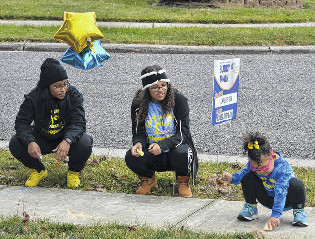Nikiya Sigman (left) and Alivea Buchanan (middle) look on as Jada Hood writes in chalk on a sidewalk near her home.