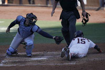 The Houston Astros' Martin Maldonado slides into home plate to score on an RBI single by Michael Brantley before Tampa Bay Rays catcher Mike Zunino can make the tag during Thursday's American League Championship Series game in San Diego. (AP photo)