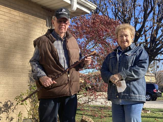 Dan Donovan, joined by his wife, Barbara, holds the antique shillelagh he used to chase burglars from the couple's Niles home even hitting one of the men in the back of the head, Tuesday, Nov. 17, 2020 in Niles, Ill. Donovan, an 81-year-old former Marine from suburban Chicago used his grandfather's antique Irish walking stick to chase off three burglars and deliver one a thump in the head for his trouble.(Jennifer Johnson/Chicago Tribune via AP)