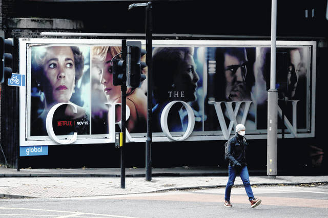 "A man wearing a face mask walks past a billboard advertising 'The Crown"" television series about Britain's Queen Elizabeth II and the royal family, during England's second coronavirus lockdown Nov. 20 in London. Britain's Culture Secretary Oliver Dowden in a newspaper interview published Sunday said he thinks ""The Crown"" should come with a disclaimer it's a work of fiction with historical liberties taken in the Netflix drama about the British royal family."