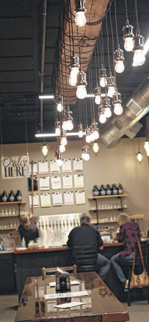 The decor of the tap room for 1820 BrewWerks in Kalida includes furniture and lighting reclaimed from older homes in Putnam County, Tessa Wehri said.