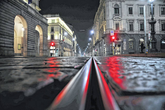 """FILE - In this Sunday, Oct. 25, 2020 file photo, an empty street in front of La Scala opera house, left, is illuminated by a red traffic light in Milan, Italy. After a rash of COVID-19 infections among musicians and chorus members, the Dec. 7 season premiere at Milan's La Scala opera house, a gala event that is one of Italy's cultural highlights, is being canceled. The theater's board of directors on Wednesday concluded that the pandemic's situation and Italy's anti-COVID-19 measures, which include closure of theaters until at least Nov. 24, won't allow for """"achieving a production open to the public and of the level and with the characteristics required"""" for the premiere."""
