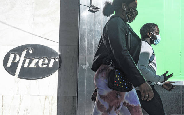 FILE - In this Nov. 9, 2020, file photo, pedestrians walk past Pfizer world headquarters in New York. Pfizer said Friday, Nov. 20, 2020, it is asking U.S. regulators to allow emergency use of its COVID-19 vaccine, starting the clock on a process that could bring limited first shots as early as next month and eventually an end to the pandemic — but not until after a long, hard winter.