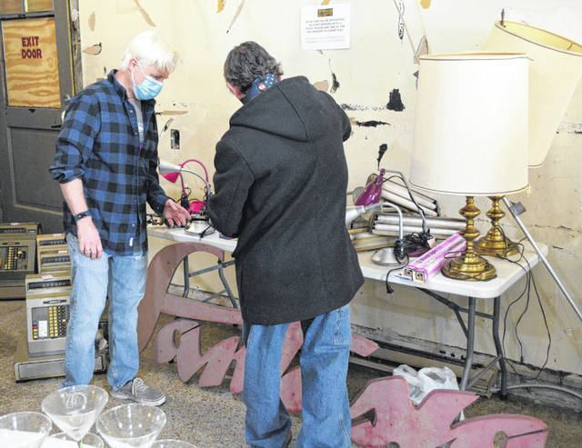 Joe Correll, the new co-owner of the Ohio Theatre, helps a customer at Saturday's Avante Garage Sale.