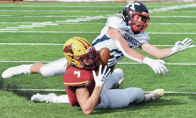 New Bremen's Wyatt Dicke comes down with the ball as John F. Kennedy's Nick Fordeley tries to break up the play at Paul Brown Tiger Stadium on Friday.