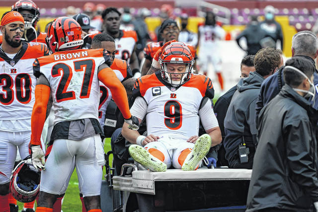 Cincinnati Bengals quarterback Joe Burrow (9) is consoled by teammates as he is carted off the field during after suffering what appeared to be a serious knee injury during a game against the Washington football team on Sunday in Landover, Md.