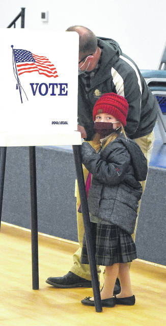 Michael Mays, of Lima, fills out his ballot as his daughter, Skyler, 5, watches democracy in action during in-person election day voting Tuesday.