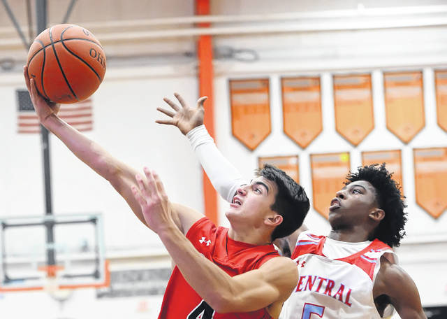 Shawnee's Brady Wheeler puts up a shot against Lima Central Catholic's DeMarr Foster during Saturday night's Mercy Health Tip Off championship game at the Elida Fieldhouse. See more Tip Off photos at LimaScores.com.