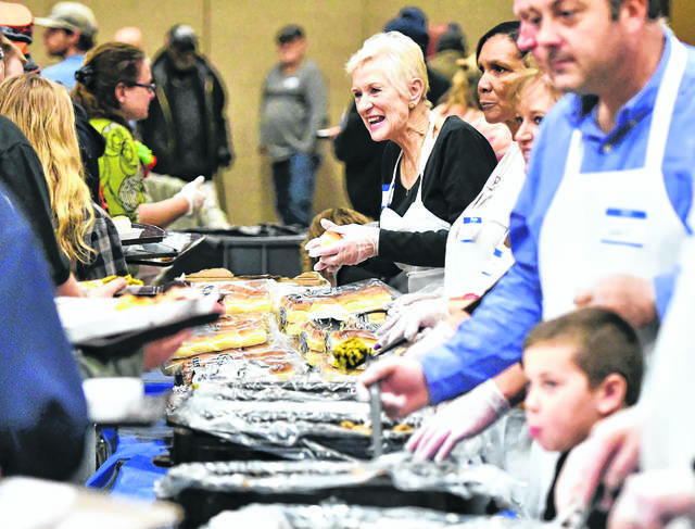 Lima Community Church volunteers serve food during a past Lima Community Thanksgiving Dinner at Veterans Memorial Civic Center.
