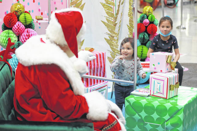 Santa Claus visits with 2-year-old Athena Hardenbrook and her 7-year-old sister, Khyla, of Ada, at the Lima Mall on Friday evening. Santa had to make adjustments to how he visits with children given the pandemic.