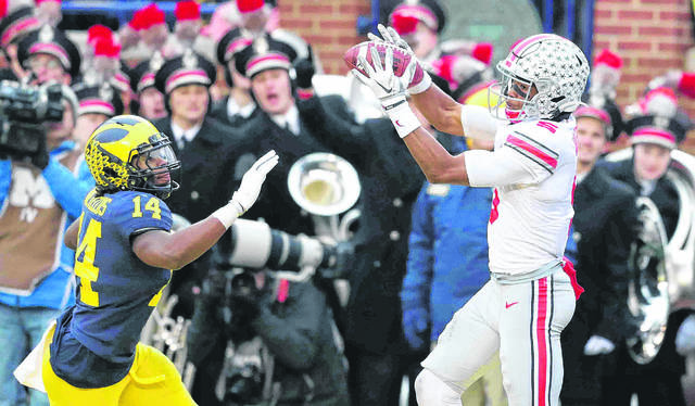 Ohio State's Garrett Wilson makes a touchdown reception against Michigan's Josh Metellus during Saturday's game in Ann Arbor, Mich. Don Speck | The Lima News