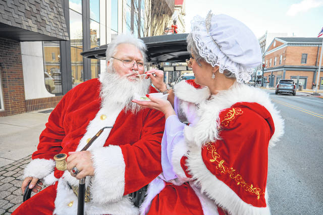 Santa and Mrs. Claus taste some local goodies  as they tour downtown Wapakoneta  on Monday afternoon, to promote Jingle Hop Sip & Shop.  The late night shopping event will be held on Friday December 4th from 5:00 p.m. to 10:00 p.m.  Amanda Wilson -The Lima News