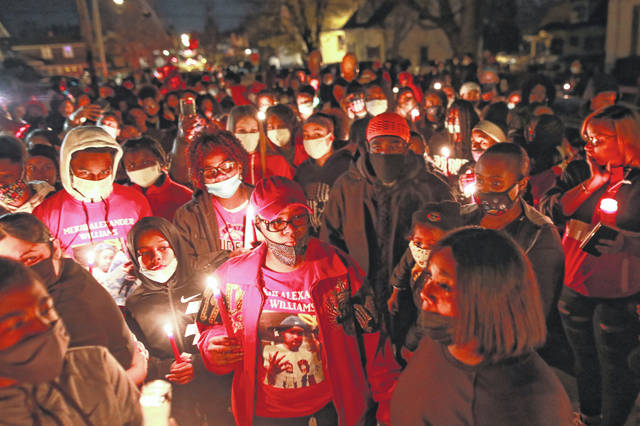 """Friends and family gather for a candlelight vigil in honor of 16-year-old Mekhi """"Khi"""" Williams, who was killed in a shooting Wedneday night. Williams' mother is in the foreground."""