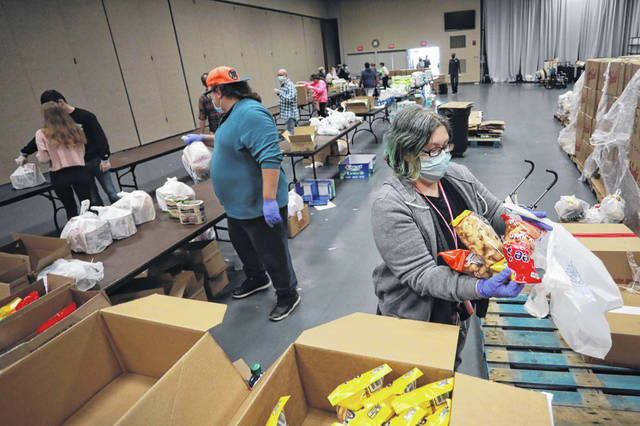 Sarah Casto and Alan Kinkead voluneer making take-home bags at the Thanksgiving Day dinner held at the Civic Center.