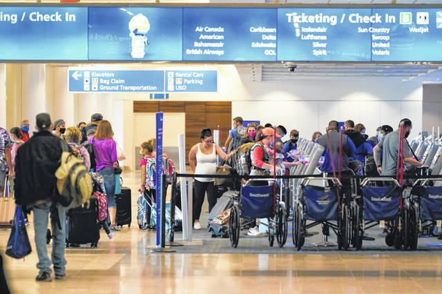 Holiday travelers check in at kiosks near an airline counter at Orlando International Airport.