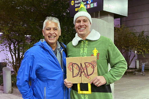 """Doug Henning, right, who was adopted as a baby, poses with his biological father after meeting face to face for the first time on Tuesday, Nov. 24, 2020, at Logan International Airport in Boston. Henning, of Eliot, Maine, wore a costume like the one actor Will Ferrell's character wore in the movie """"Elf"""" and he broke into the same awkward song from the movie while meeting his father. (Rebecca Taylor Henning via AP)"""