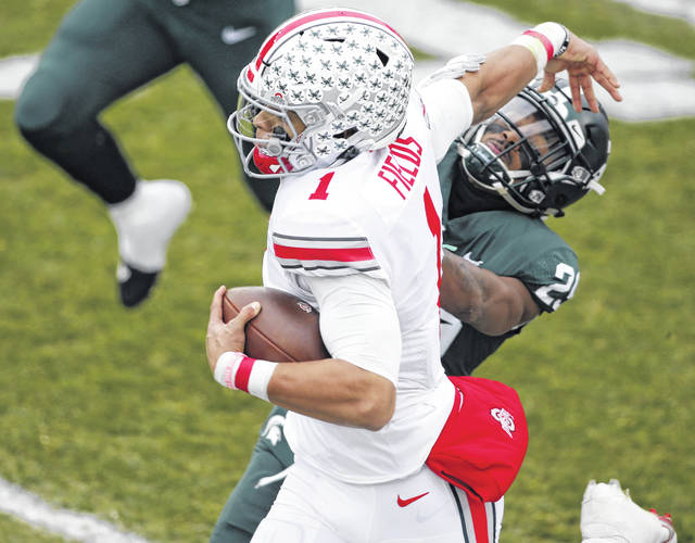 Ohio State's Justin Fields pushes away Michigan State's Shakur Brown during Saturday's game in East Lansing, Mich.