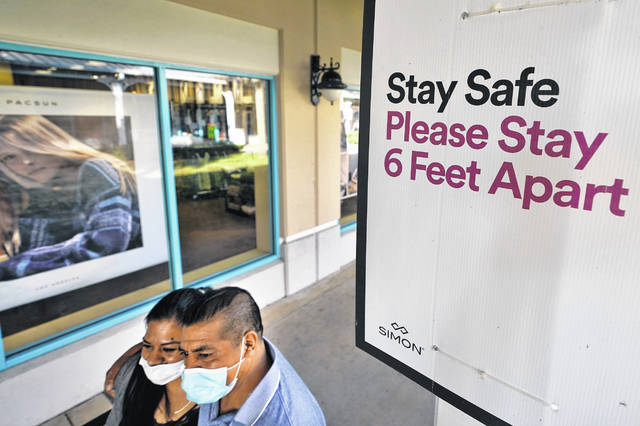 Shoppers wear protective face masks Nov. 27 as they walk past a social distancing sign at the Ellenton Premium Outlet stores in Ellenton, Fla. Social distancing mandates have hindered the medical exams that are often required for life insurance applications. As a result, insurers increasingly use big data to decide who gets life insurance and at what price.